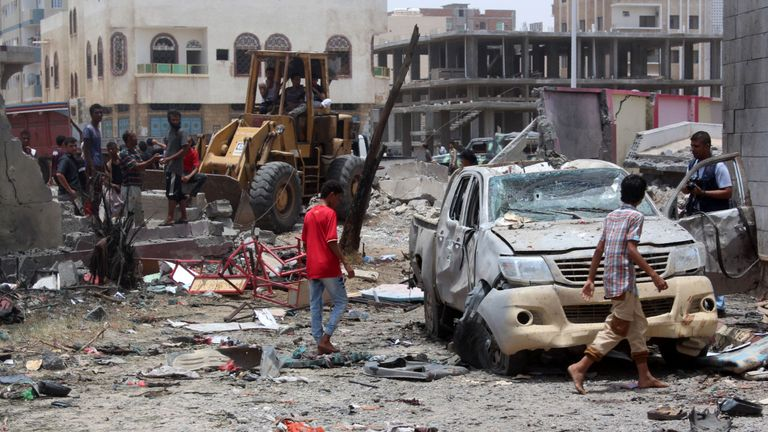 Yemenis inspect the site of a suicide car bombing claimed by Islamic State