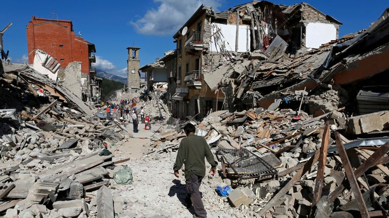 A man walks amid the devastation in Pescara del Tronto