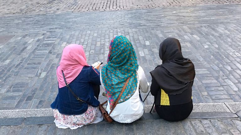 Three young Muslim women in headscarves sit on a kerb in London