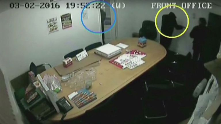 Screen grabbed image taken from CCTV issued by West Midlands Police of an armed hooded gunman (circled) pointing a gun at Akhtar Javeed in the front office of the Direct Source 3 warehouse in the Digbeth area of Birmingham, which was shown to a jury in the Javeed murder case at Birmingham Crown Court.