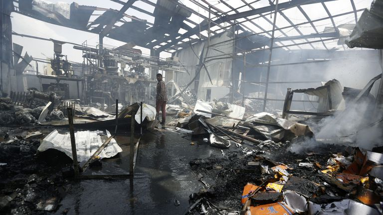 An employee walks inside a factory after a Saudi-led airstrike in Yemen