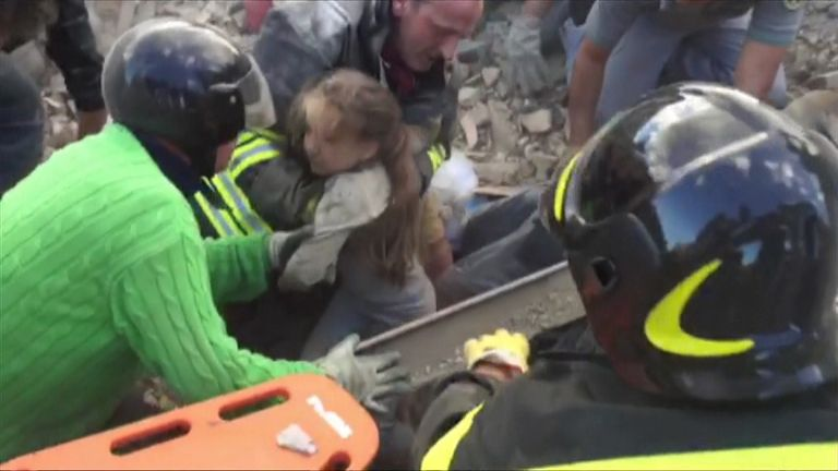 A young girl is pulled from under the rubble