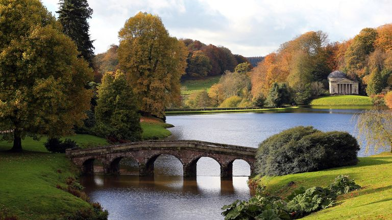 STOURHEAD, ENGLAND - NOVEMBER 02: The sun shines on trees that are displaying their autumn colours surrounding Palladian bridge and the lakeside Pantheon at the National Trust's Stourhead on November 2, 2012 in Wiltshire, England.