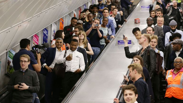 Mayor of London Sadiq Khan (left) and travellers go down the escalators at Brixton Underground station