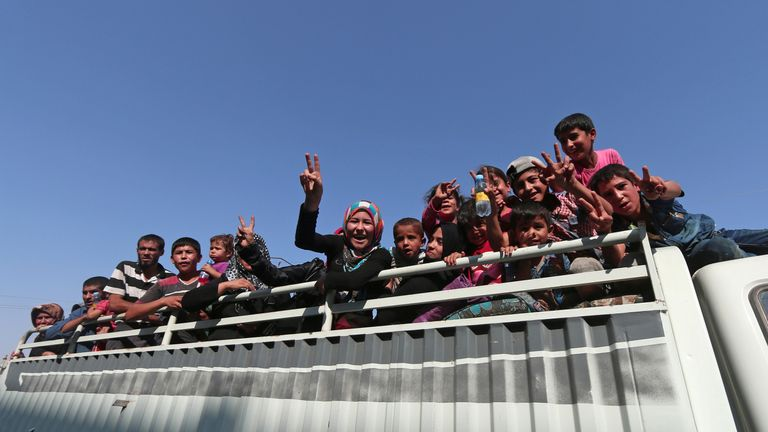 Civilians react atop of a pick-up truck after they were evacuated by the Syria Democratic Forces (SDF) fighters from an Islamic State-controlled neighbourhood of Manbij, in Aleppo Governorate, Syria