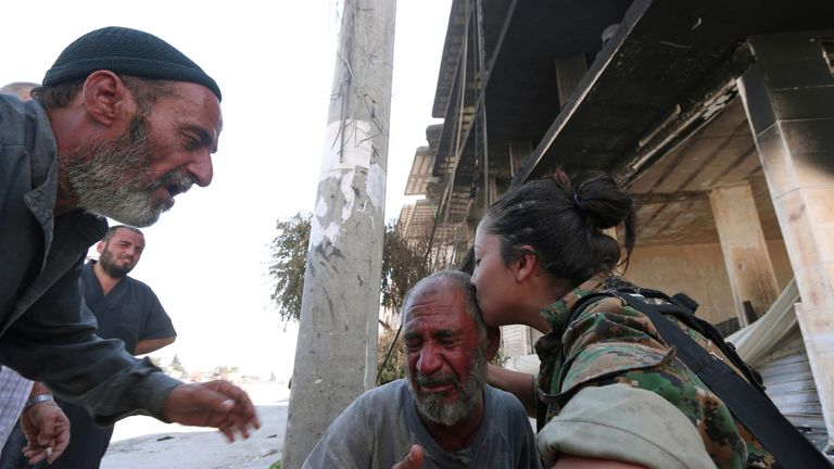 A Syria Democratic Forces (SDF) fighter comforts a civilian who was evacuated with others by the SDF from an Islamic State-controlled neighbourhood of Manbij, in Aleppo Governorate, Syria on 12.08.16