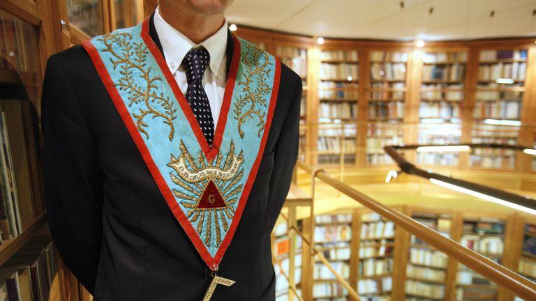 A worshipful master poses in his masonic regalia at a grand lodge