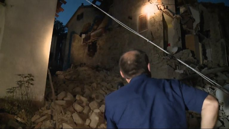 A Police Officer searches rubble in a town hit by the earthquake