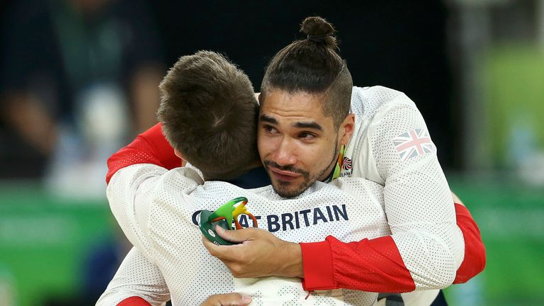 Silver medallist Louis Smith of Britain hugs gold medallist Max Whitlock on the podium