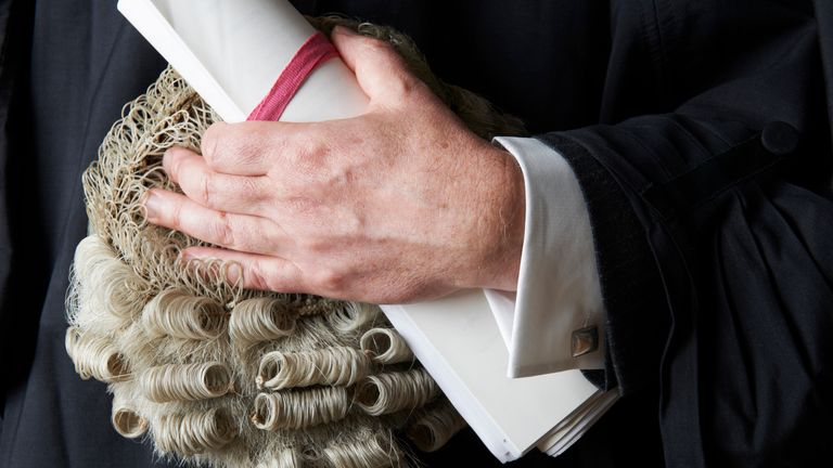 A barrister holding his brief and wig