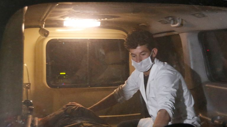 A wounded man is treated in an ambulance outside the campus