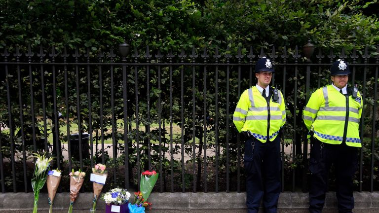 Flowers rest against railings near the scene of a fatal stabbing in Russell Square, London