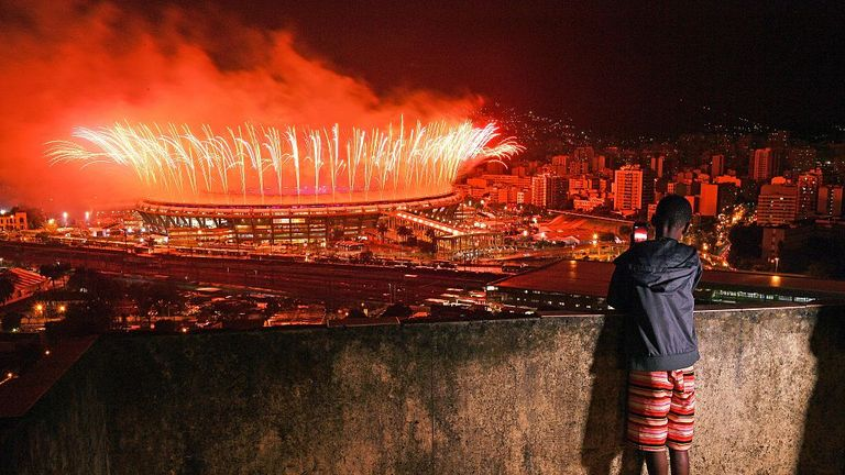 A boy from Mangueira favela watches fireworks over Maracana Stadium during the 2016 Olympics closing ceremony in Rio