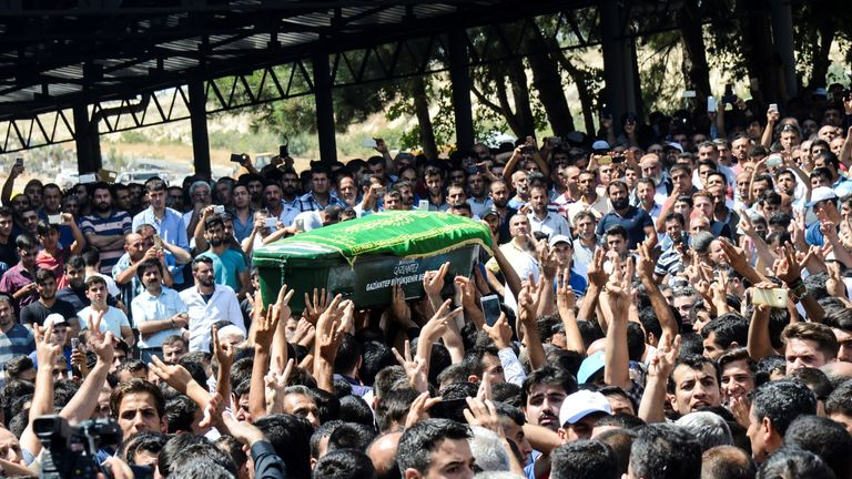 People carry the coffin of one of the victims to a funeral