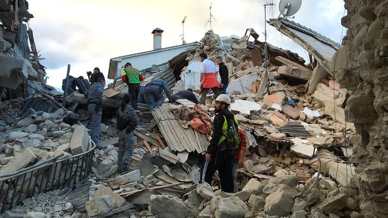 Rescuers search through the rubble of a collapsed house in Amatrice