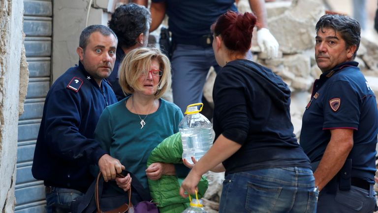 A woman in tears as she is led to safety after being rescued from her home