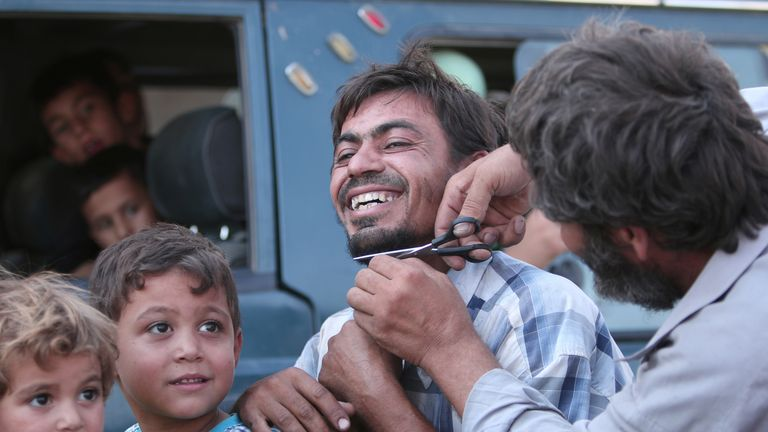A man cuts the beard of a civilian after Manbij freed
