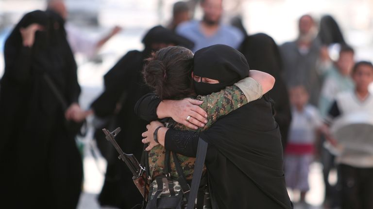 A woman hugs  an SDF fighter after she is evacuated from Manbij