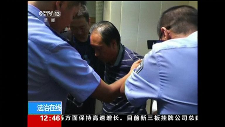 The suspect (centre) surrounded by police officers