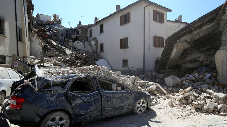 A destroyed car is seen following an earthquake in Amatrice