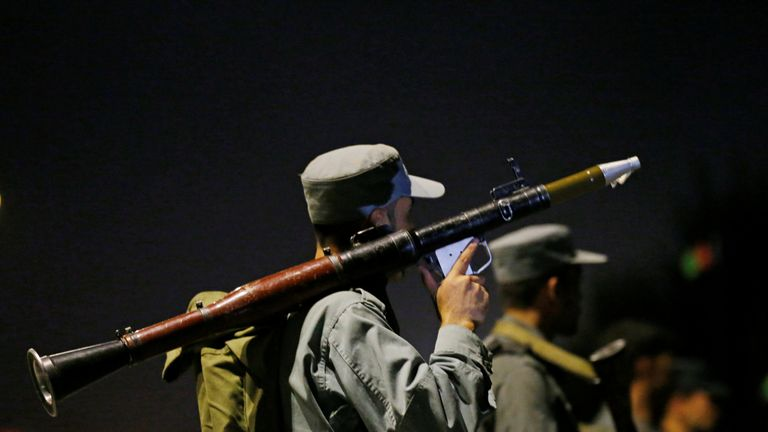 An Afghan police officer stands outside the campus