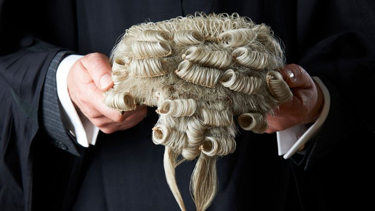 A barrister holding his wig