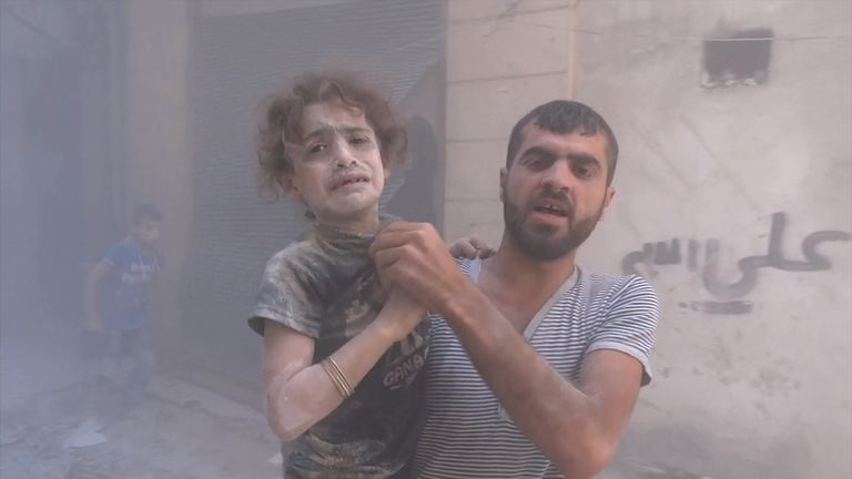 A man holds a young girl after an airstrike in eastern Aleppo.