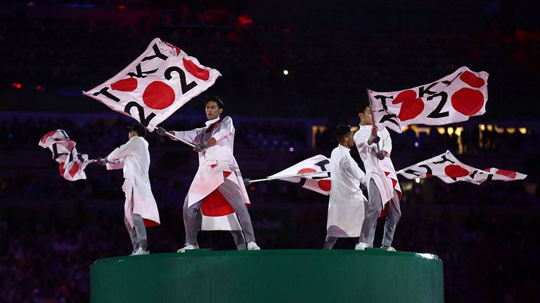 Flags emblazoned with Tokyo 2020 waved at the Rio Games closing ceremony