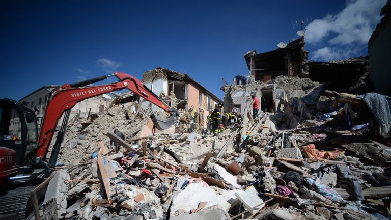 TOPSHOT - Rescuers and firemen inspect the rubble of buildings in Amatrice on August 24, 2016 after a powerful earthquake rocked central Italy.   The earth
