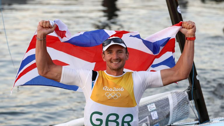 Great Britain's Giles Scott poses with a flag at the Maria da Gloria