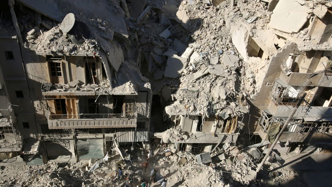 People dig in the rubble in an ongoing search for survivors at a site hit previously by an airstrike in rebel-held Tariq al-Bab in Aleppo, Syria
