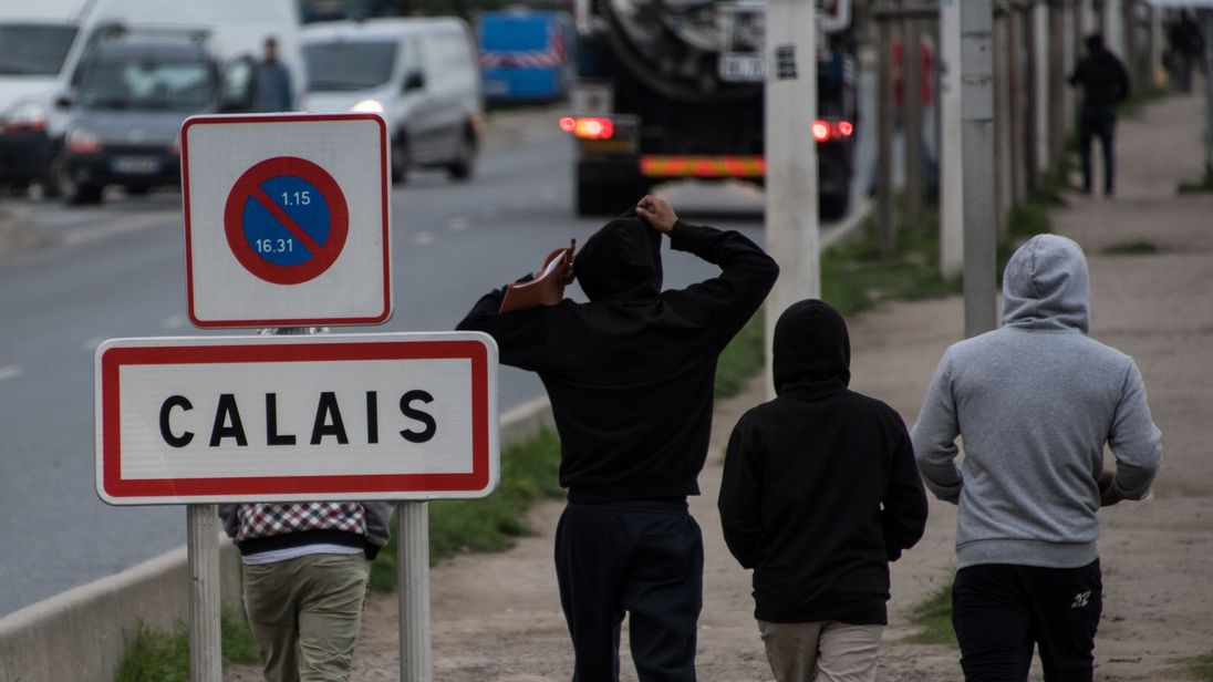 Migrants living in the 'Jungle&#39 migrant camp walk past a sign posted along a road that leads to the town of Calais in northwestern France