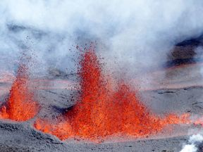 """A molten lava spray after a volcanic eruption from """"The Peak of the Furnace"""" (Le Piton de la Fournaise) in the eastern side of the on the French Indian Ocean island of La Reunion."""