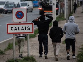 Migrants living in the 'Jungle' migrant camp walk past a sign posted along a road that leads to the town of Calais in northwestern France on September 26, 2016, French President Francois Hollande said on a visit to the port of Calais that the sprawling 'Jungle' migrant camp would be 'definitively dismantled' under a plan to relocate the migrants to centres around the country. / AFP / DENIS CHARLET (Photo credit should read DENIS CHARLET/AFP/Getty Images)