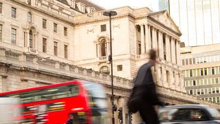 A cyclist rides past the Bank of England