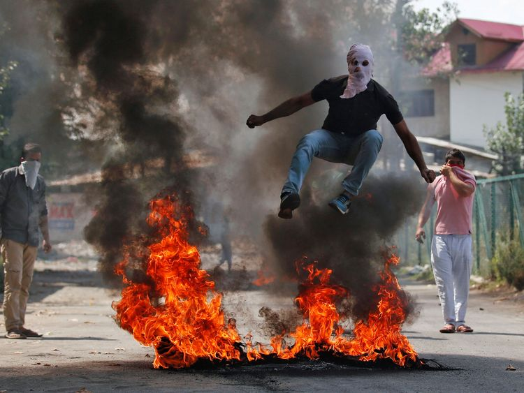 A man in a balaclava jumps over burning debris in Srinagar, India, during a protest against the recent killings in Kashmir