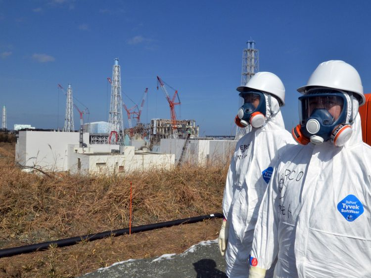 Workers stand on front of the Fukushima power plant months after a meltdown at the site