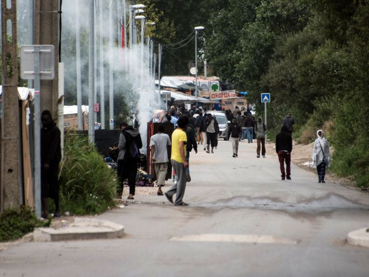 Migrants walk on September 26, 2016 in the so-called 'Jungle' migrant camp in the French northern port city of Calais. French President Francois Hollande said on a visit to the port of Calais on September 26, 2016 that the sprawling 'Jungle' migrant camp would be 'definitively dismantled' under a plan to relocate the migrants to centres around the country.
