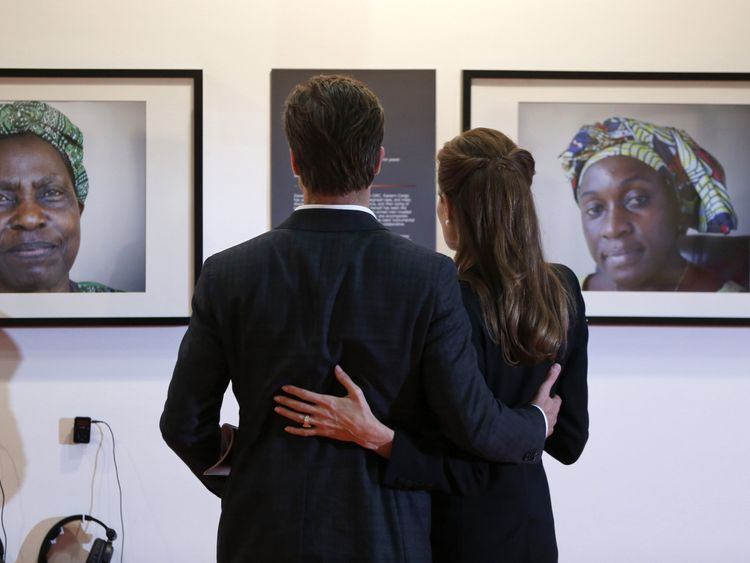 Jolie and Pitt looking at pictures of victims of violence during the Global Summit to End Sexual Violence in Conflict in London in 2014