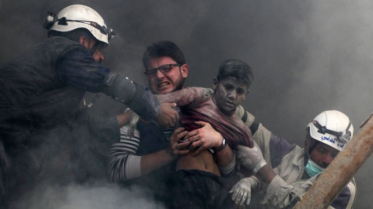 A boy is pulled from rubble after an alleged barrel bomb strike in al Shaar, Aleppo