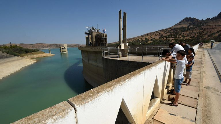 A photo taken on August 21, 2016 shows Tunisians looking at the Sidi Salem dam near Testour, in Tunisia's north-west Beja region, which has particularly low water levels due to a 30 percent drop in rainfall in the North African country this year. Water-cuts, dry dams and withering vegetation: Tunisia has faced a difficult summer due to a lack of rainfall which has reinforced social tensions in several disadvantaged regions. / AFP / FETHI BELAID / TO GO WITH AFP STORY BY MOUNIR SOUISSI (Photo cre