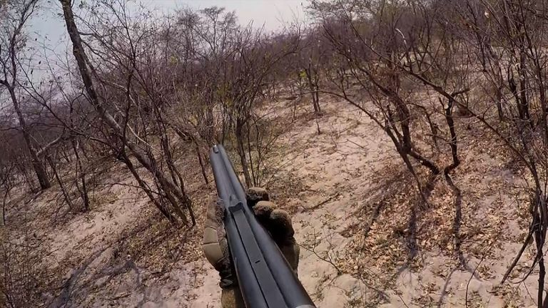 A trophy hunter aims a gun at an elephant in Namibia