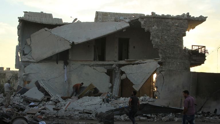 People inspect damage after an airstrike