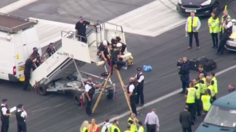 Police officers work to remove a demonstrator from a tripod on the runway