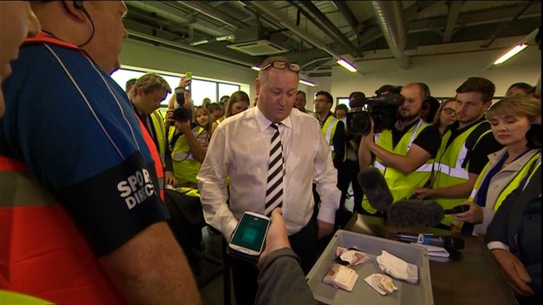 Mike Ashley takes a wad of cash out of his pocket during the Sport Direct tour