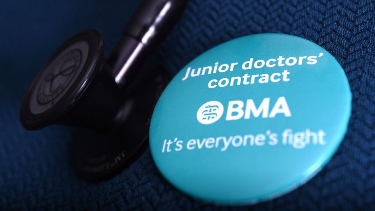 Junior doctor wearing a badge about contract dispute