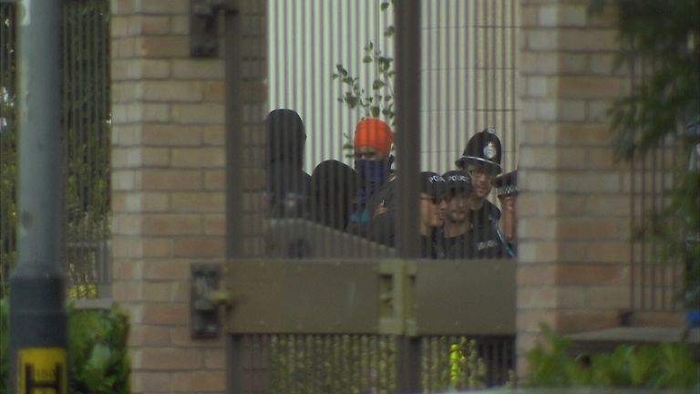 A group of masked men talk to police officers outside the Leamington gurdwara
