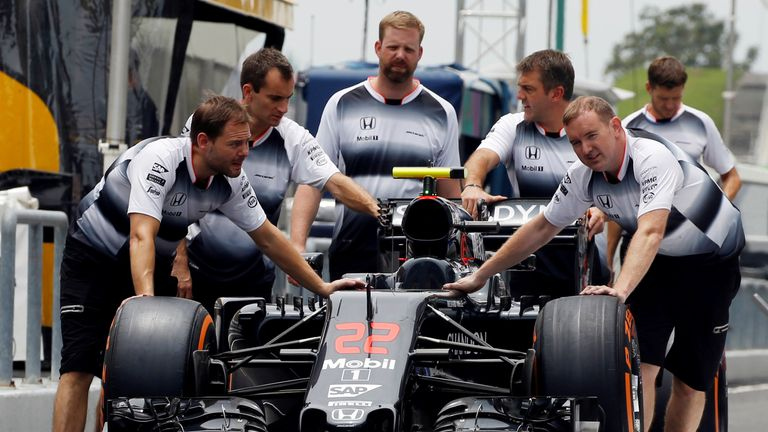 Crew members push Jenson Button's McLaren into the pits ahead of the Malaysian Grand Prix