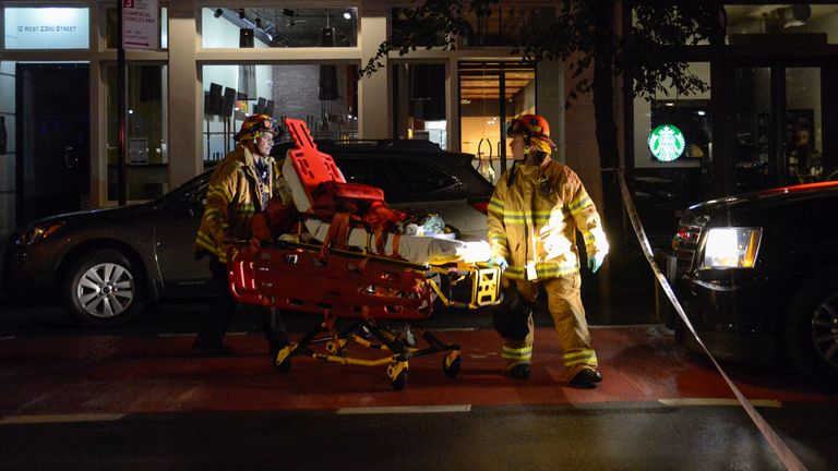 Firefighters use a wheeled stretcher to carry supplies near the site of an explosion
