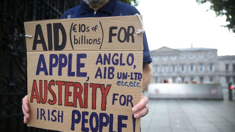 A protester holds a placard outside the hearing at Leinster House, Dublin.